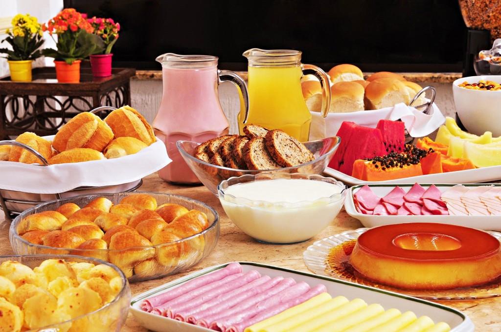 mesa-de-café-da-manhã-com-frutas-pães-sucos-bolos-e-iogurt